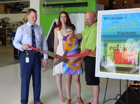 Eelsnot Marine Coatings CEO Toby West (right) cuts the ribbon to his new Norge storefront with his family and James City County Office of Economic Development Director Russell Seymour. (Courtesy James City County)