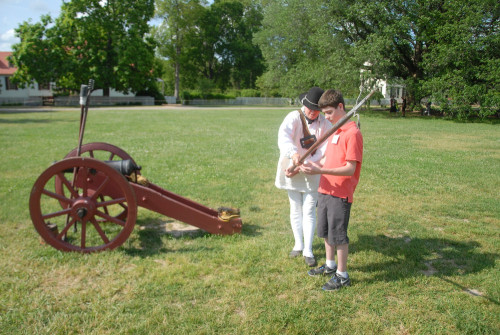 Colonial Williamsburg Historical Interpreter Carrie MacDougall shows 14-year-old Caleb Fenderson how to use a linstock. The linstock is used to light the fuse on a cannon. (Gregory Connolly/WYDaily)