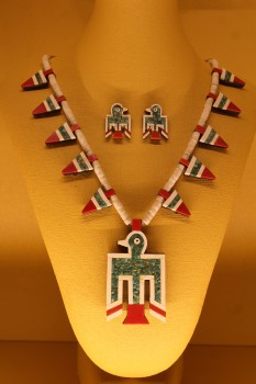 An example of a thunderbird necklace and matching earrings, made of plastic, turquoise and gypsum beads.