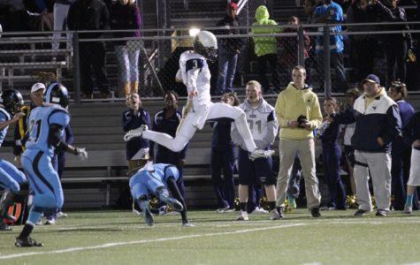 Lafayette quarterback Brendan McGinty hurdles a Warhill defender. (file photo)