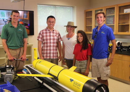 The Aqua Kids pose for a photo while filming a scene on underwater gliders with VIMS Assistant Professor Donglai Gong. (Courtesy Virginia Institute of Marine Science)