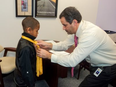 """Bethel Manor Principal Mike Lombardo helps a student, Quentin Royster, adjust his tie on """"Tie and Tiara Tuesday."""" (YCSD)"""