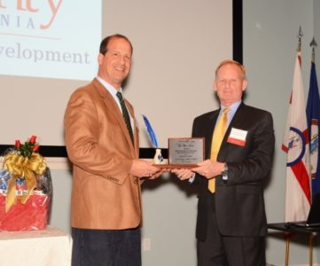 """(Left) Steve Miller, Co-owner of Pritchard & Miller Real Estate Development, receives the """"Poor Potter"""" Award from Anderson Moberg (right), Chairman of the York County Economic Development Authority. (Photo courtesy of York County)"""
