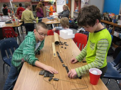 Declan Walsh (left) and Timofey Dyakov set up dominoes Feb. 23, 2016 as part of the Rube Goldberg contraption Norge Elementary students are creating for an international competition. (Kirsten Petersen/ WYDaily)