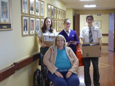 Veritas Preparatory School students Emma Blackford, Katie Rose Beatovich and Paulo Chisari deliver a donation to Consulate Health Care's Envoy of Williamsburg residents. (Courtesy Rebecca Greenwood)