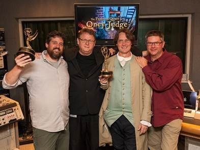 Colonial Williamsburg employees Wayne Hill and Charles White hoist Emmy awards. (Photo courtesy of Colonial Williamsburg)