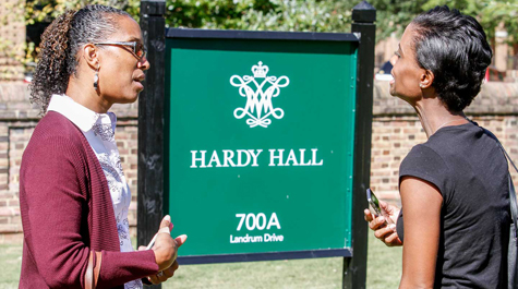Two of the ceremony's attendees stand near the sign for Hardy Hall. (Photo by Skip Rowland '83)