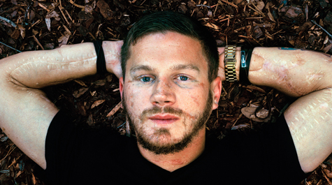 Kyle Carpenter lies under the oaks of the University of South Carolina's Horseshoe. A Medal of Honor winner, he is enrolled as a student studying international relations. (Eliot Dudik, courtesy of The War Horse/W&M News)