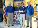 Diane Fry, USO Center Director, receiving checks from Lions Don Brannon and Jim McBriarty.
