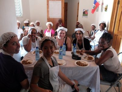 W&M student Jiajia Chen, front, and fellow alternative breakers eat with their hosts in Cap-Haïtien, Haiti last month. (Photo courtesy Jose Acuna)