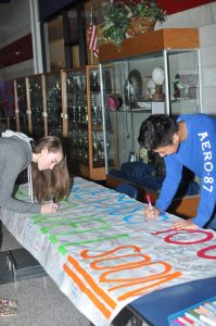 Grafton High School students Lainey Griffin and Fred Choi sign a banner Wednesday for freshman Andrew Stonier, who is recovering from a heart transplant. (Photo courtesy Holly Conradi)