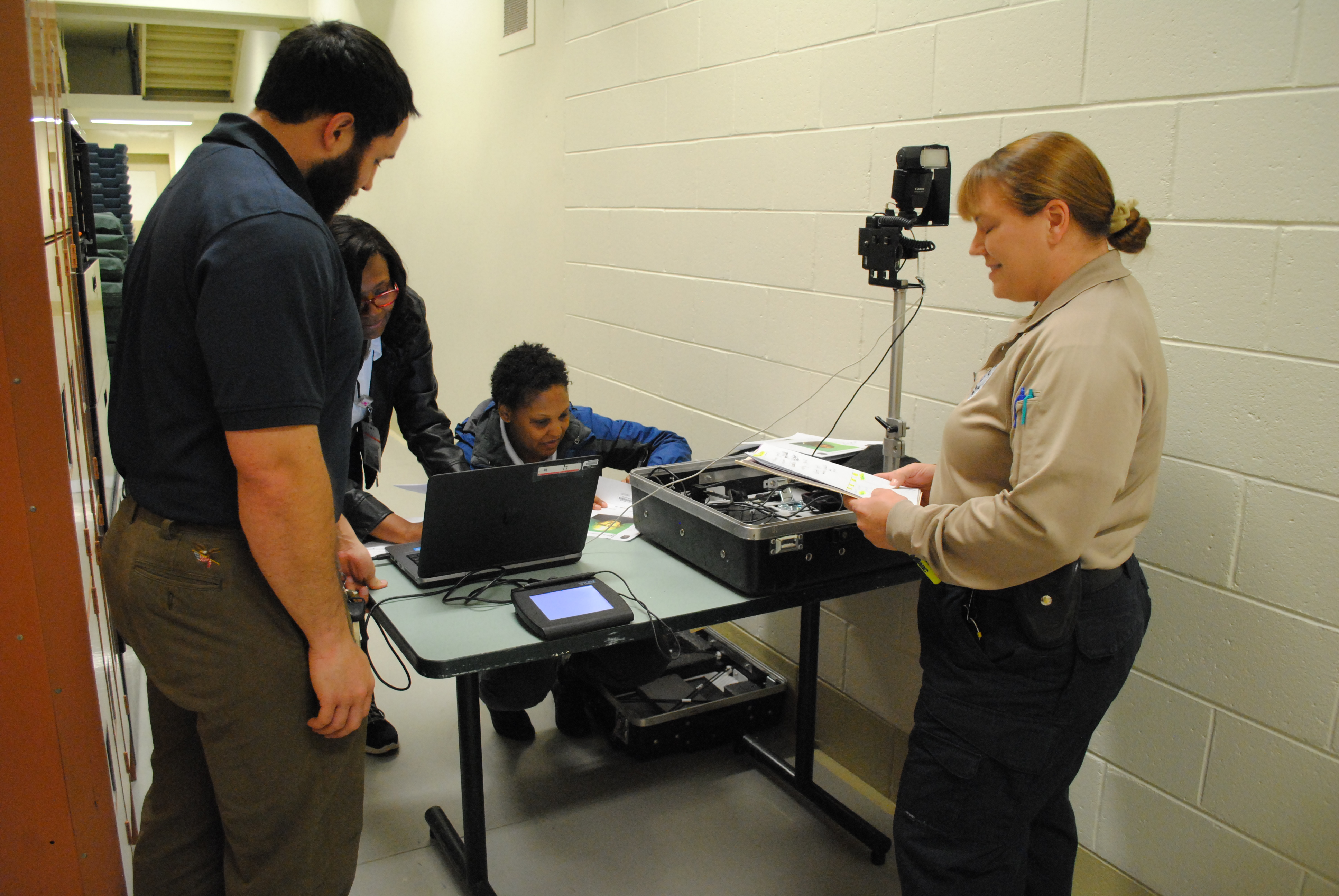 DMV employees Eddie Chandler, Jeraye Booth and Latasha Hill set up a mobile ID card station at the Virginia Peninsula Regional Jail. Cpl. Christina McCain (right) runs the program at the jail. (Sarah Fearing/WYDaily)