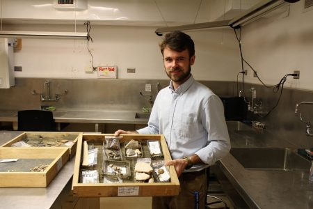Assistant Curator Hayden Bassett holds a tray of artifacts removed from the floor of the church. (Andrew Harris/WYDaily)