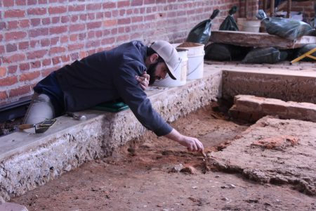 Archaeologist Bob Chartrand removes APVA backfill as he defines one of the church's many burial shafts. (Andrew Harris/WYDaily)