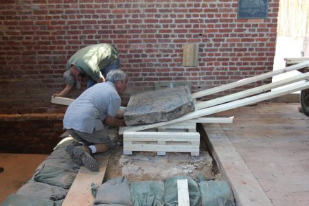 Jonathan Appel (gray shirt) and the Preservation Virginia team used wooden levels and a wooden ramp to move the Knight's Tomb from its spot on the church floor to a place where conservation work can be done. (Courtesy Hayden Bassett)