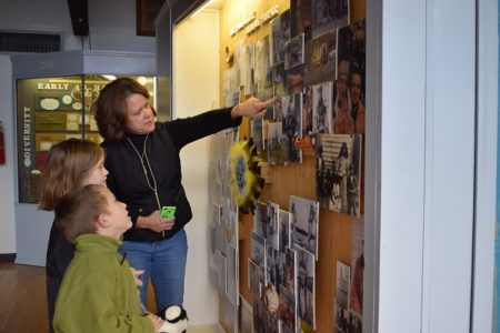 Pamunkey woman Kim Cook Taylor shows young visitors a collage of past and present members of the Pamunkey Tribe. Photo courtesy Ben Swenson