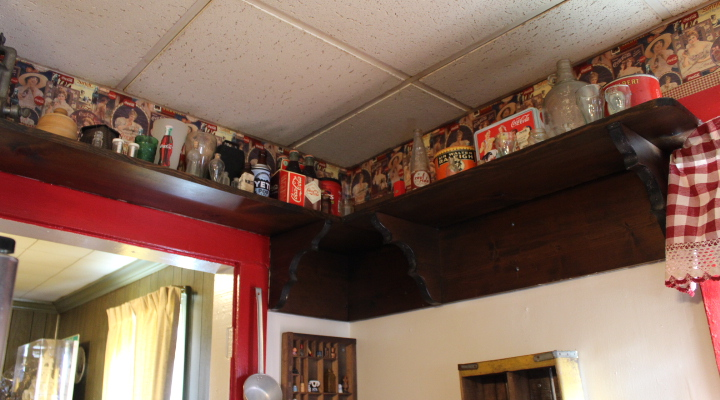 Dozens of Coca Cola collector's items line kitchen shelves, matching the room's red checkered curtains. (Sarah Fearing/WYDaily)