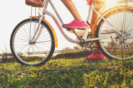 close up leg woman on bicycle with sunset at park