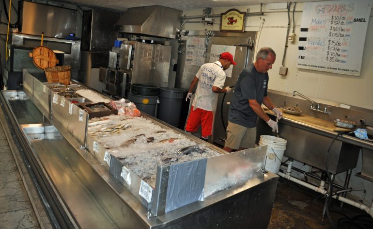 Kevin Seldon, right, peels shrimp and talks about seafood fraud (Rami Yoakum/Southside Daily)