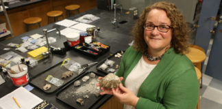 """William & Mary archaeologist Jennifer Kahn examines artifacts from one of her numerous excavations of human sites in the islands of Oceania. Kahn contributed knowledge from Hawaii, Micronesia and Polynesia to a synthesis paper in """"Science"""" that challenges the traditional notion of the Anthropocene. (WYDaily/Courtesy of Stephen Salpukas)"""